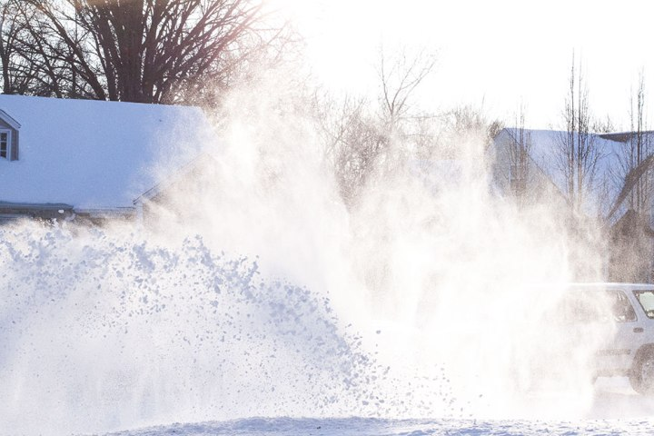 snow blower kansas winter with sun flare
